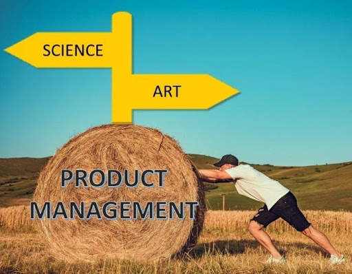person pushing a hay bale in front a sign post pointing towards science instead of art